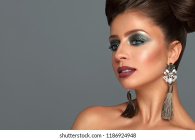 Sexy girl with her hair up, high hair. Elegant woman with big shiny earrings. Portrait of a beautiful model on grey background