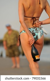 sexy girl hiding back champagne bottle and two wine glasses