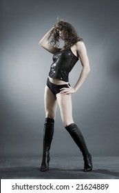 sexy girl in high boots posing against dark background