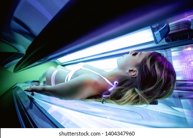 Sexy girl inside a solarium getting tanned skin