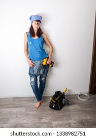 The sexy girl the jack of all trades stands against the white wall and holds in her hands a yellow screwdriver. A tool bag stands against the wall.