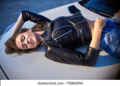 sexy girl in a leather jacket, denim shorts and black pantyhose in the net lies on the hood of the car