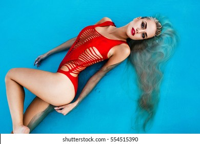 sexy girl with long blonde hair and red lips in swimming pool