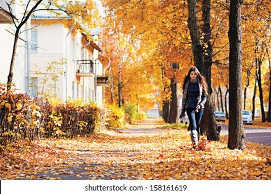 Sexy girl with long hair walking down a street full of fallen golden and red leaves during autumn time in jeans, jacket, high boots and scarf