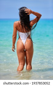 Sexy girl with long hair in a white swimsuit walking at the tropical beach in Thailand