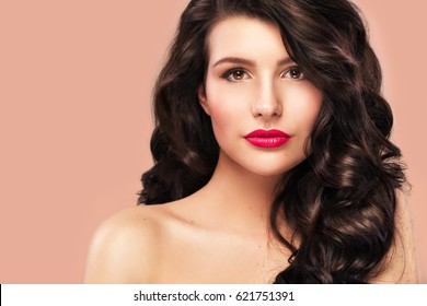 Sexy girl with long and shiny wavy hair . Beautiful model, curly hairstyle on orange background.