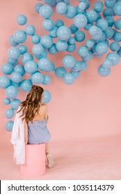 A sexy girl with loose hair and a blue dress and a pink blouse in her arms is in a pink room and sits with her back on a pink barrel