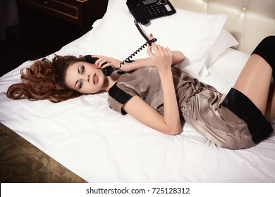Sexy girl lying on the bed with phone