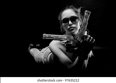 Sexy girl lying on the floor with guns