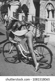 Sexy girl with naked buttocks rides bicycle, urban background. Attractive brunette sit on bicycle. Sexy tourist concept.