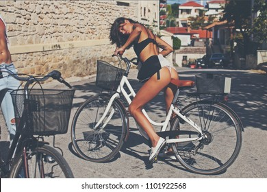 Sexy girl with naked buttocks rides bicycle, urban background. Attractive brunette sit on bicycle. Sexy tourist concept. Sexy woman ass. Sensual woman. LIfestyle. Adult. Beauty woman. Sport. Fitness.