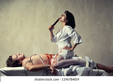 Sexy girl in nurse uniform with knife and bonded man on the bed