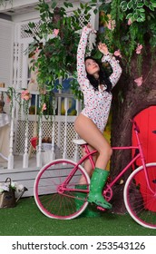 Sexy girl on a bicycle breaks petals from a tree