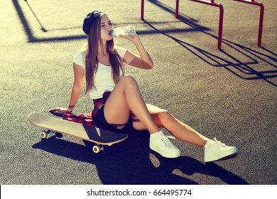 Sexy girl in on sports ground drink water