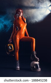 Sexy girl in orange latex catsuit with helmet and camera, sci-fi setting