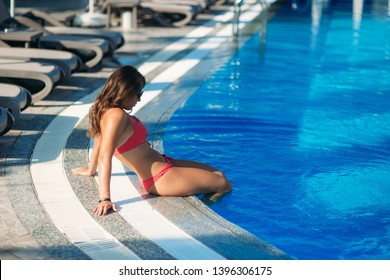Sexy girl in a pink bathing suit sunbathing by the swimming pool