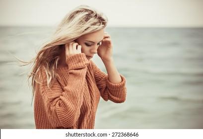 sexy girl poses on a beach. beautiful blonde enjoys walk on the coast