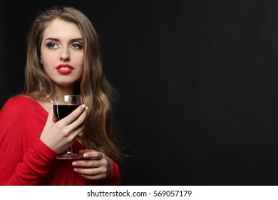 Sexy girl posing with a glass of wine in her hand on a dark background.