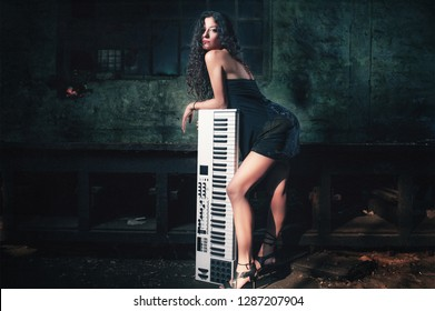 Sexy girl posing with the music keyboard and controller in the grungy environment place. Girl musician and keyboard player concept.