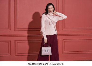Sexy girl is posing on the coral wall background in a studio. She wears a pink sweater, marsala pants, fancy earring. Woman holds a lilac bag and looks downward. Horizontal.