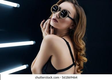 sexy menina posando no estúdio contra fundo preto com lâmpadas, vestindo óculos de sol. Mulher de moda alegre com brilhante maquilagem, lábios vermelhos em óculos de sol, calcinha preta e um sutiã preto