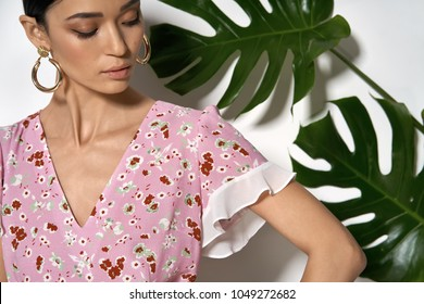 Sexy girl is posing in a studio on a background of a white wall with big green leaves. She wears a pink dress with flower prints and massive round earrings. Woman looks downward. Closeup. Horizontal.