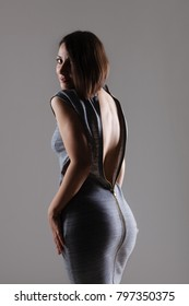 sexy girl posing with unzipped dress on the back