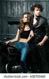 sexy girl or pretty woman with stylish blond, long hair sitting on vintage motorcycle and handsome, young man in garage on dark grey wooden background. biker couple in love, Wanderlust and adventure