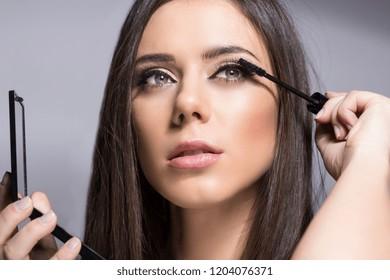 sexy girl putting mascara on eyelashes.beauty make up