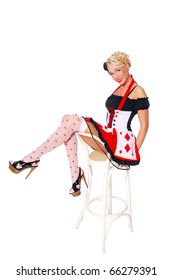 Sexy girl in a queen of hearts costume sit on the chair and show long legs