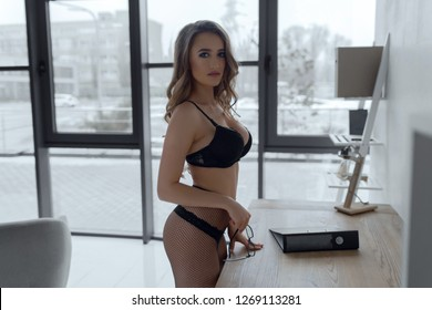 Sexy girl secretary with beautiful breasts dressed in black lingerie and pantyhoses posing in the office.