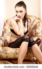 Sexy girl is sitting in a chair.