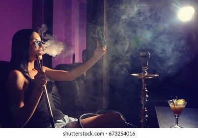 Sexy girl smokes hookah and makes selfie