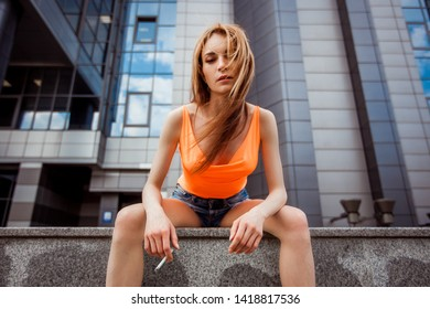 Sexy girl Smoking a cigarette on the street