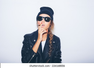 Sexy girl  in sunglasses and black leather jacket smoking cigar.  White background, not isolated