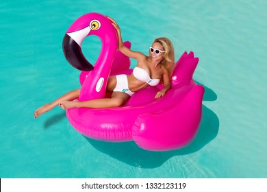 Sexy girl sunglasses having fun in the pool floating on a large inflatable pink flamingo in a hotel on summer vacation on a tropical island. The concept of summer leisure freedom of pleasure - Image