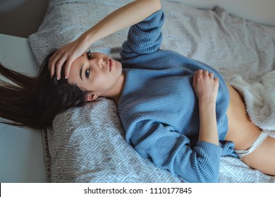 Sexy girl in sweater lying on the bed and looking to the camera