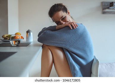 Sexy girl in a sweater sitting on bar chair and smiling