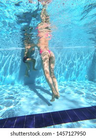 Sexy girl in a swiming pool with a kid. Underwater view