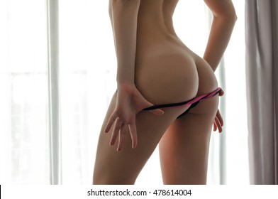 Sexy girl takes off her panties. Seductive naked woman standing with her back to the camera and shows a beautiful ass. It is the boudoir shoot in bedroom with big window.