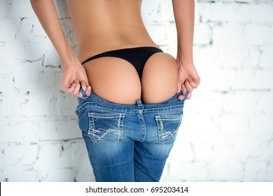 Sexy girl takes off her jeans. Seductive woman standing with her back to the camera and shows a beautiful ass.