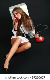 Sexy girl talking by red vintage phone.