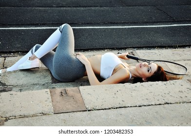 Sexy girl with tennis racquet lying on the sports ground