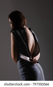 sexy girl with unzipped dress holding cleaver knife behind her back