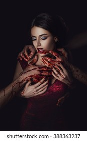 Sexy girl vampire in passionate embrace man's hands, stained with blood, the girl in a red dress, a fashionable toning, creative color