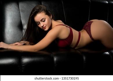 Sexy girl in vinous lingerie on the sofa view