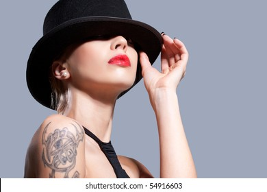 Sexy girl wearing a black hat, isolated on grey