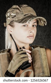 Sexy girl wearing military style posing with guns and sunglases isolated in studio