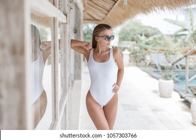 Sexy girl in a white bathing suit rests near a tropical villa