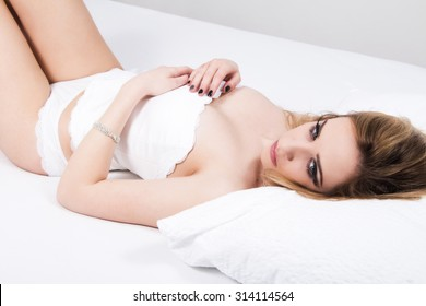 Sexy girl in white corset and panties underwear lying on the bed